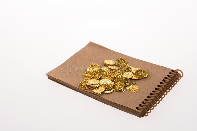 Blocco note a spirale e le monete di oro immagine stock libera da diritti