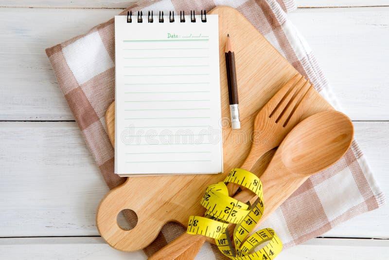 Blocco note sul tagliere con una forchetta e un cucchiaio ed i meas di legno fotografia stock libera da diritti