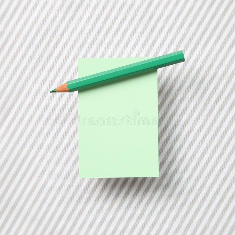 Blocco note verde dell'appunto e matita colorata verde sul fondo del tessuto fotografia stock libera da diritti