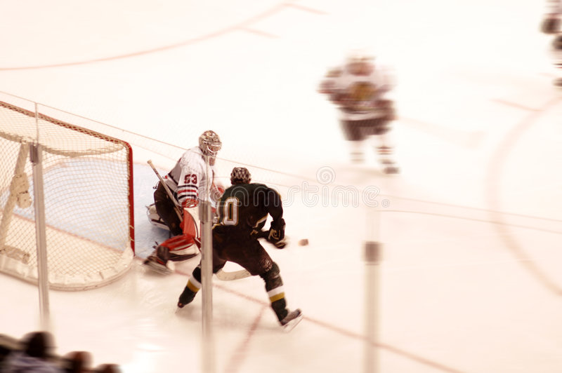 Block. Goalie blocks a shot from another hockey player stock image