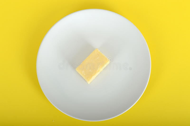 Block of Cheddar Cheese. Cheddar Cheese on a Plate against a Yellow Background royalty free stock images