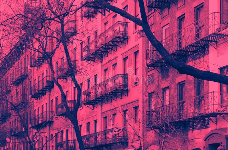 Block of colorful old buildings in the Upper East Side neighborhood of New York City in pink and blue royalty free stock image