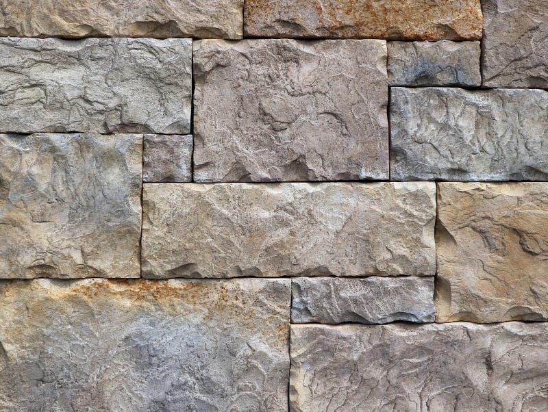 Block formte die Steinwand, die von den Felsen mit verschiedenen geometrischen Formen hergestellt wurde Hintergrund und Beschaffe lizenzfreies stockbild