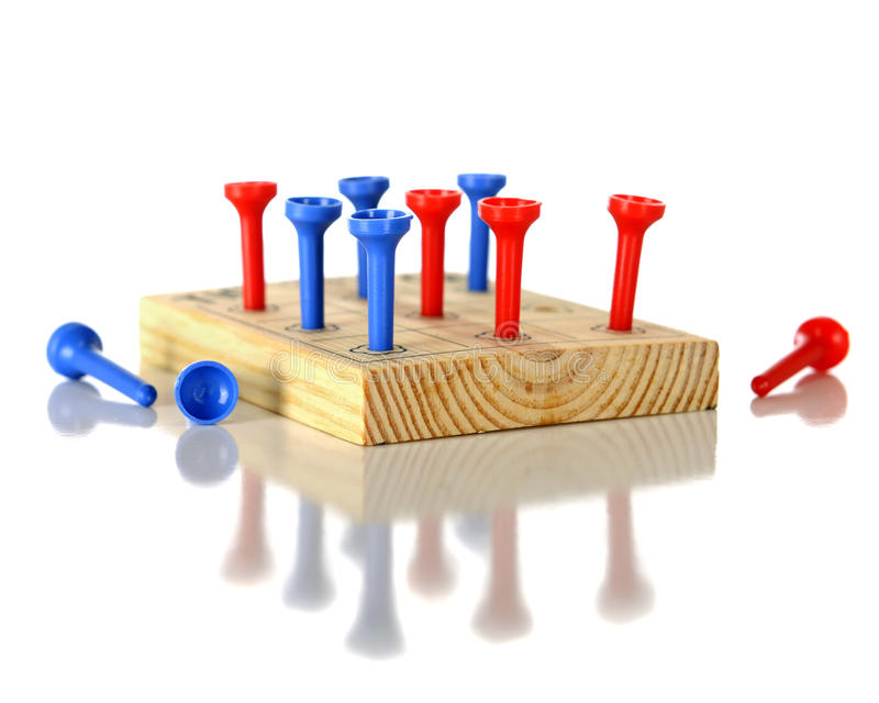 Block and Peg Game. Closeup view of a wooden block game with red and blue plastic pegs. On a white background. Reflected off the white surface royalty free stock images