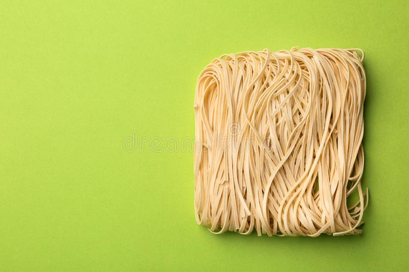 Block of quick cooking noodles on color background, top view. Space for text stock image