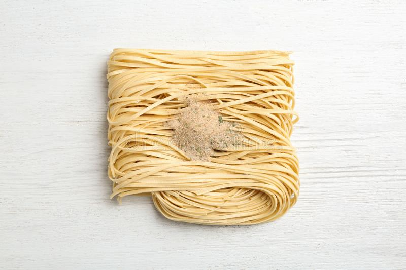 Block of quick cooking noodles with spices on wooden background, royalty free stock photography