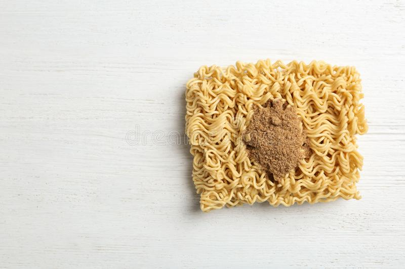 Block of quick cooking noodles with spices on wooden background. Space for text royalty free stock photos