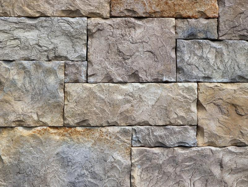 Block shaped stone wall made of rocks with different geometric shapes. Background and texture royalty free stock image