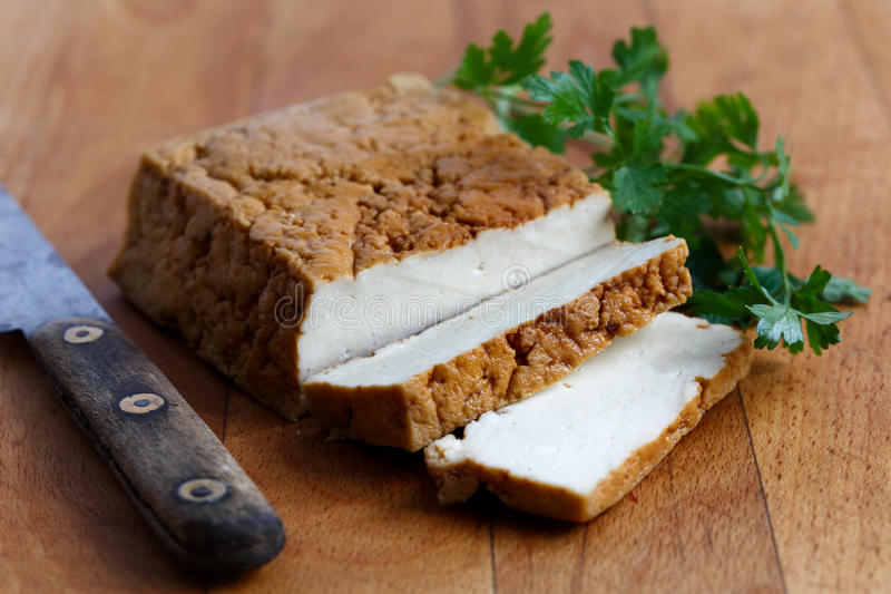 Block of smoked tofu, two tofu slices, rustic knife and fresh p stock photography