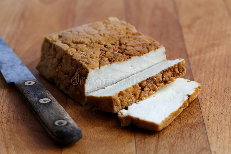 Block of smoked tofu, two tofu slices and rustic knife on wooden stock photography