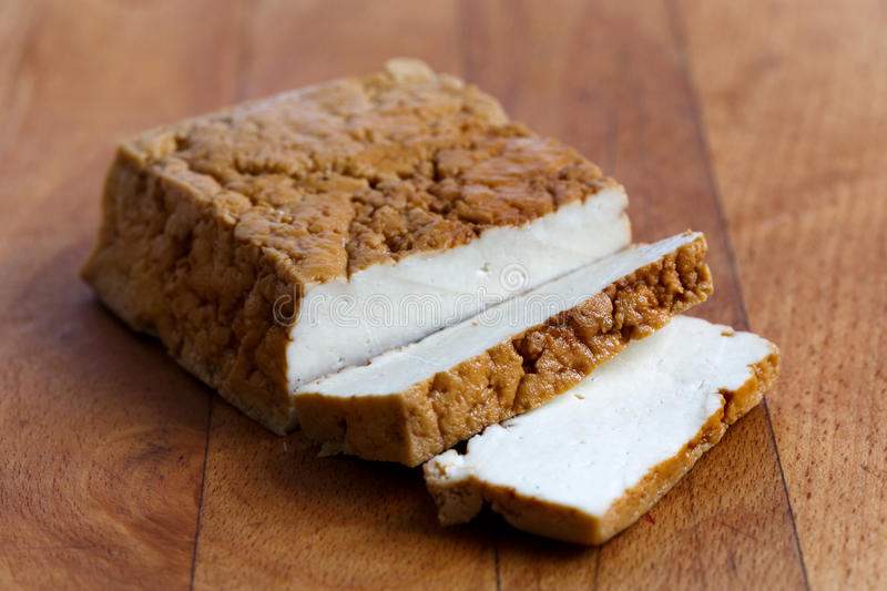 Block of smoked tofu and two tofu slices on wooden chopping boar royalty free stock photography