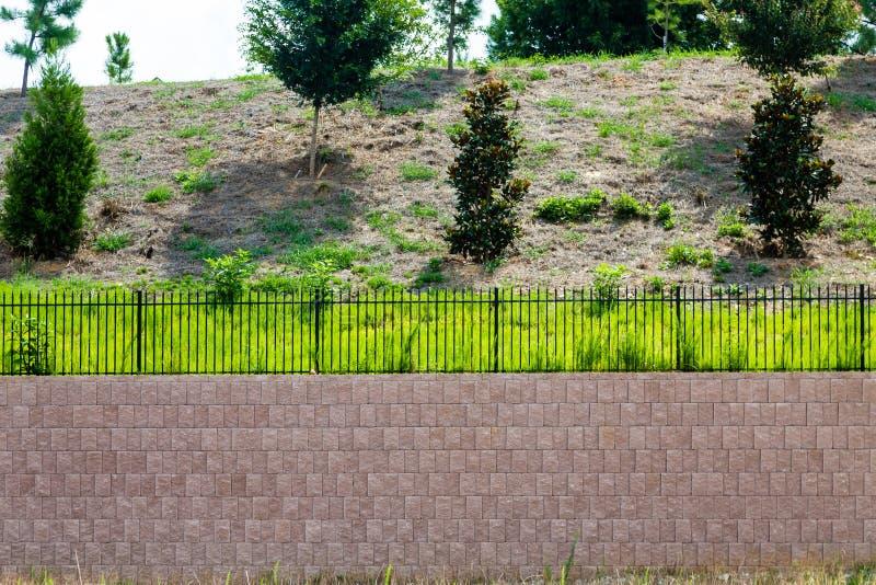 Block-Stützmauer überstiegen mit schwarzem Eisen-Zaun lizenzfreie stockfotos
