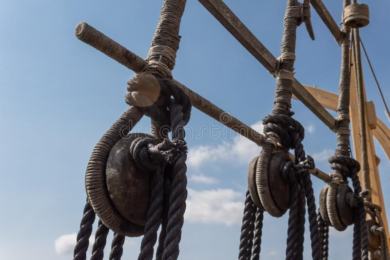 Block and tackle rigging on an old tall ship before blue sky, spliced and wrapped rope lines. Horizontal aspect royalty free stock image