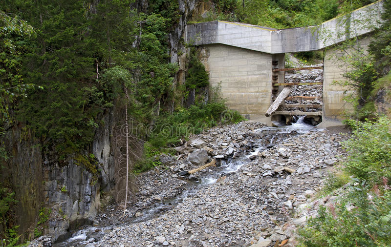 Blockage of a torrent control. Concreted blockage of a torrent control with stuck tree trunk stock images