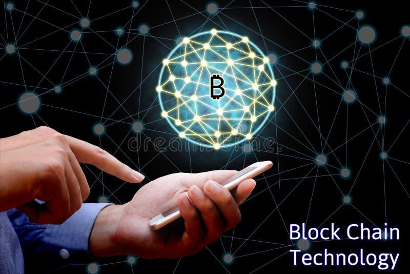 Blockchain技术概念,拿着智能手机的商人  库存图片