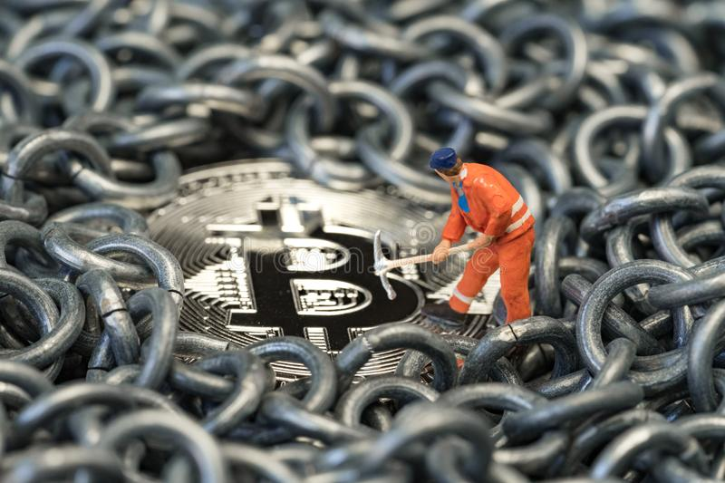 Blockchain and Bitcoin mining by miniature worker, small mini figure holding mattock digging on physical Bitcoin Crpto currency c stock photo