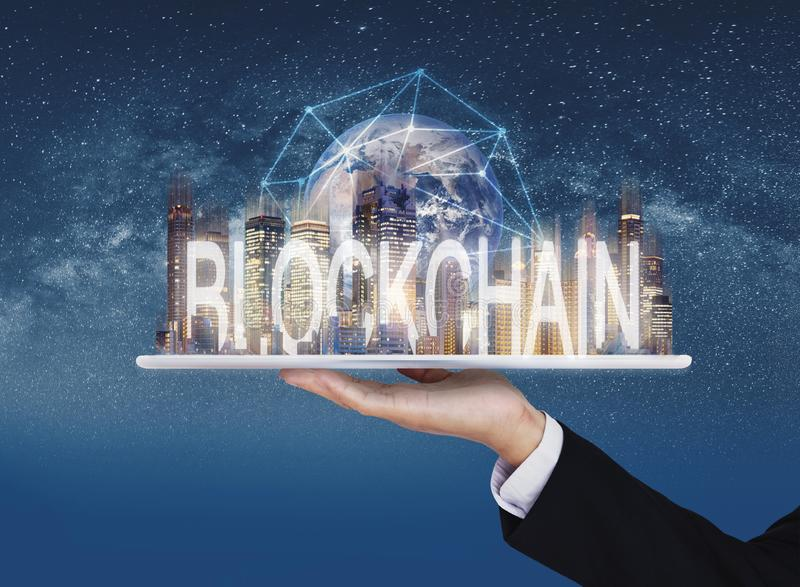 Blockchain business and technology, Hand holding digital tablet with buildings and blockchain technology. Element of this image ar stock photos