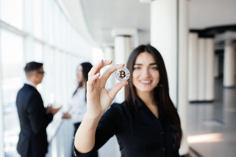 Blockchain e conceito do investimento Líder da mulher de negócio que guarda o bitcoin na frente de discutir a equipe no escritóri imagem de stock royalty free
