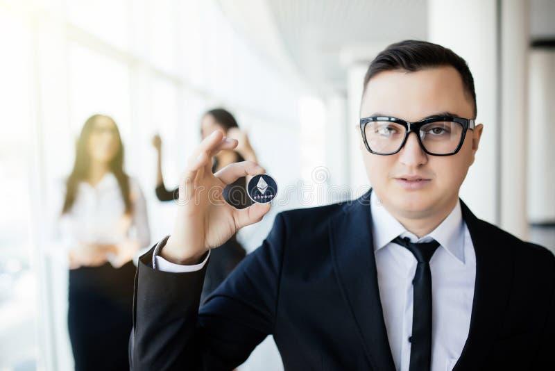 Blockchain e conceito do investimento Líder do homem de negócio que guarda o litecoin na frente de sua equipe com mãos levantadas foto de stock royalty free