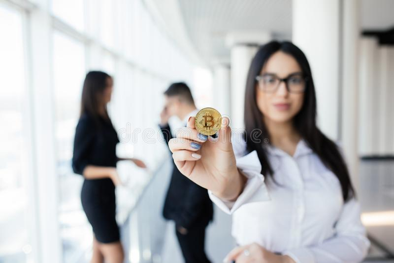 Blockchain et concept d'investissement Chef de femme d'affaires tenant le bitcoin devant discuter l'équipe sur le bureau photos stock