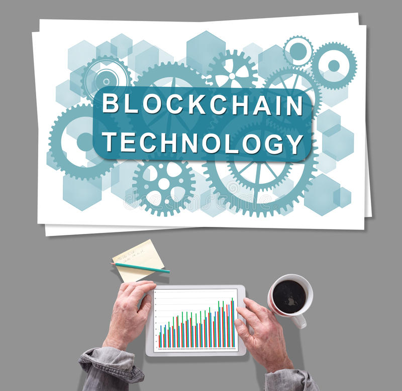 Blockchain technology concept placed on a desk. Male hands using tablet in front of blockchain technology concept royalty free stock photo