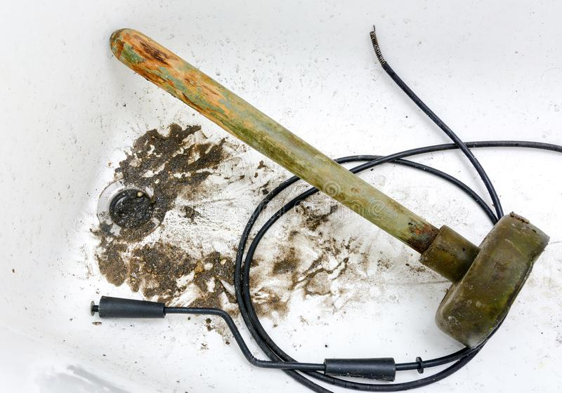 Blocked sewer in the bathroom. Bath plug old plunger and plumbers tools stock image