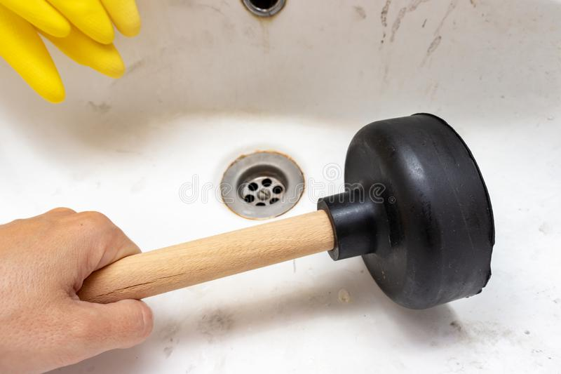 Blocked sewer, clogged wash bowl, basin drain, yellow rubber gloves and a hand holding a plunger in the bathroom at home, plumbing. And maintenance concept royalty free stock photography
