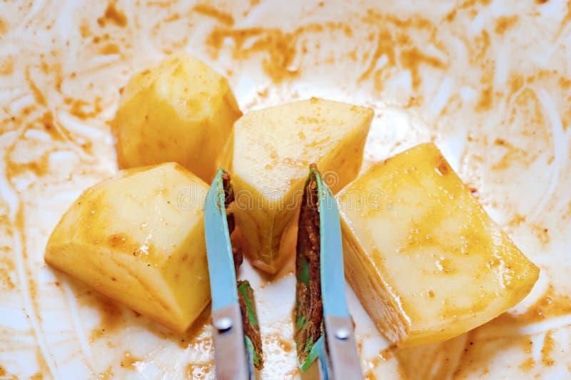 Blockierung die Zangen und Kartoffeln mariniert in einer weißen Schüssel bereit zum Grillen, zur Röstung oder zum Backen stockfoto