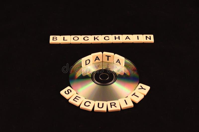 Blockkettensicherheit buchstabierte heraus in den Fliesen um eine CD mit den Daten, die in der Mitte auf einem schwarzen Hintergr lizenzfreie stockfotografie