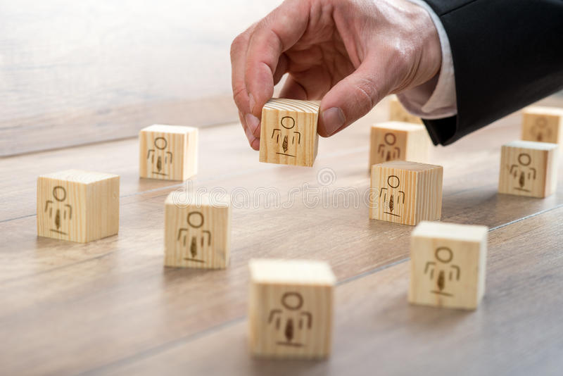 Blocks for Customer-Managed Relationship Concept. Customer-Managed Relationship Concept - Businessman Arranging Small Wooden Blocks with Symbols on the Table royalty free stock photos