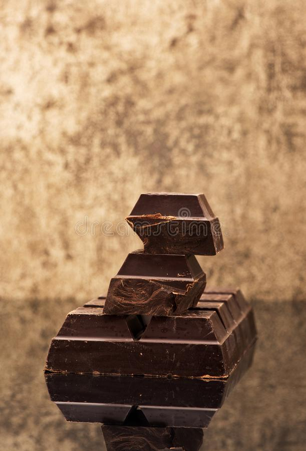 Blocks and pieces dark chocolate on a stone background. Background royalty free stock photography