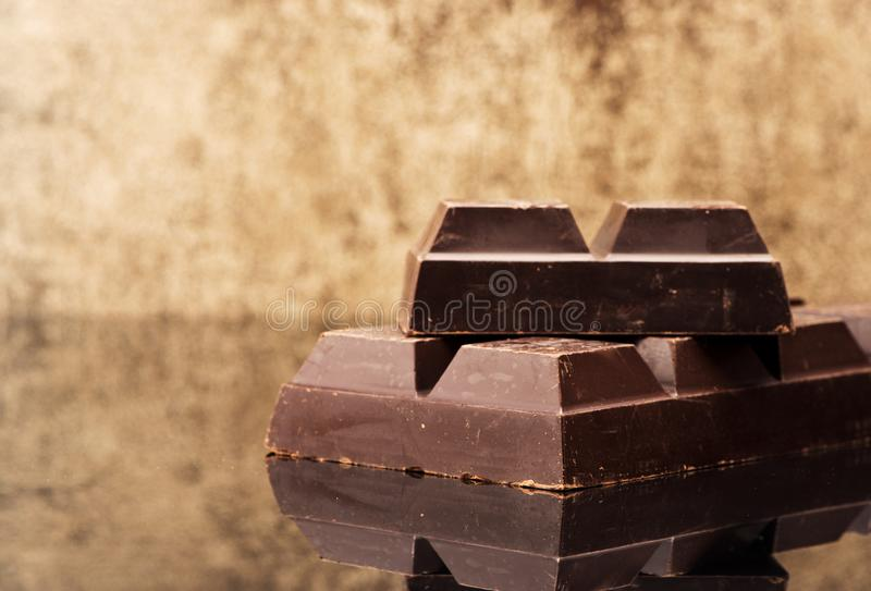 Blocks and pieces dark chocolate on a stone background. And copy space for text stock images