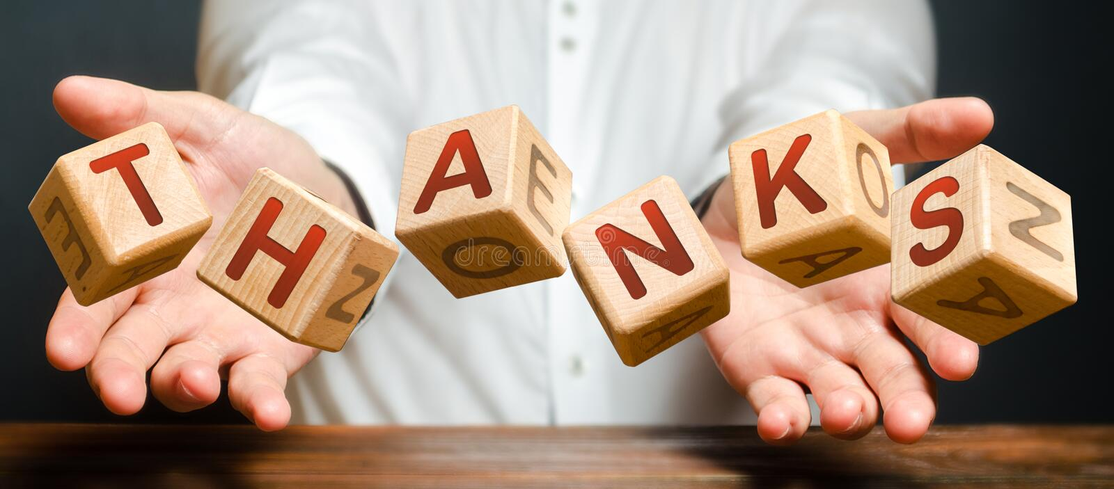 Blocks thrown by a man with letters form the word Thanks. The person brings his thanks and appreciates the service or help royalty free stock photo