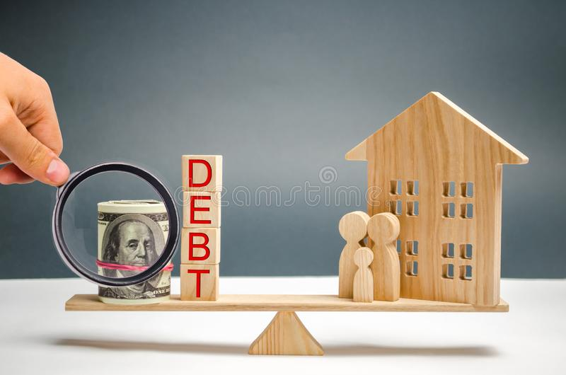 Blocks with the word debt and money, family and wooden house. Real estate, home savings, loans market concept. Payment of real royalty free stock photos