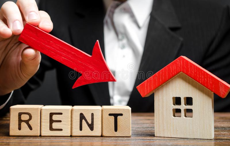 Blocks with the word Rent, down arrow and a miniature house. The concept of reducing the price of renting a house or apartment. stock photo