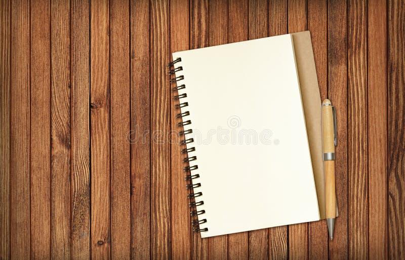Blocnote en een potlood op bruin hout stock foto