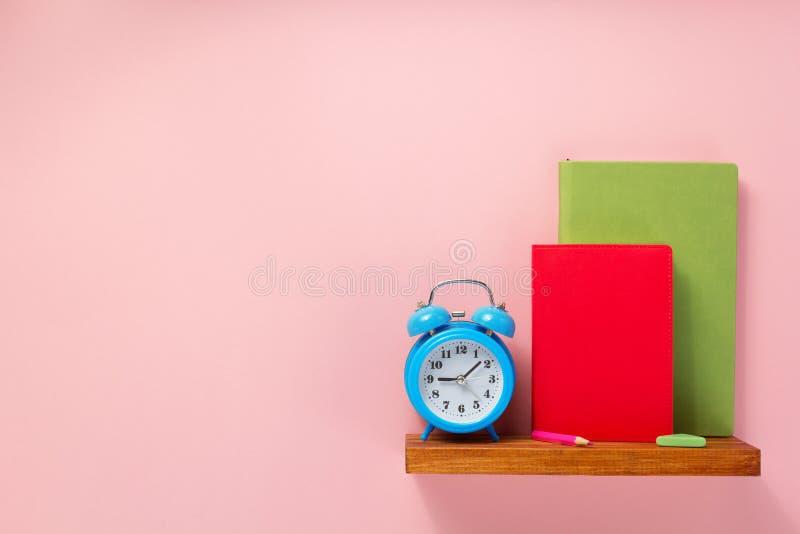Blocnote en wekker op plank bij muurachtergrond stock foto