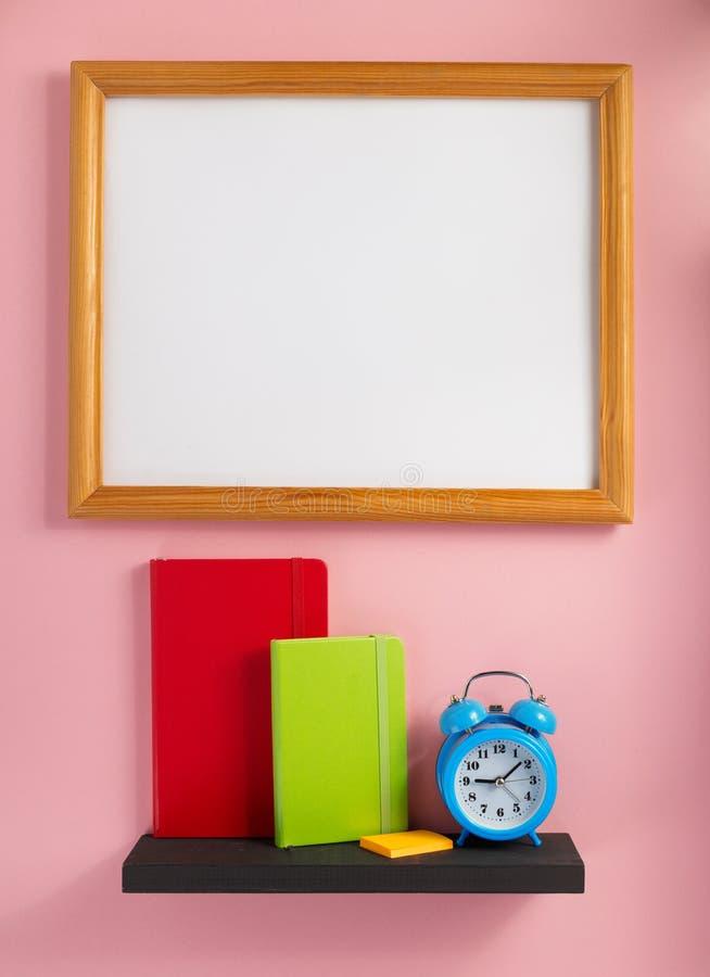 Blocnote en wekker op plank bij muurachtergrond stock fotografie