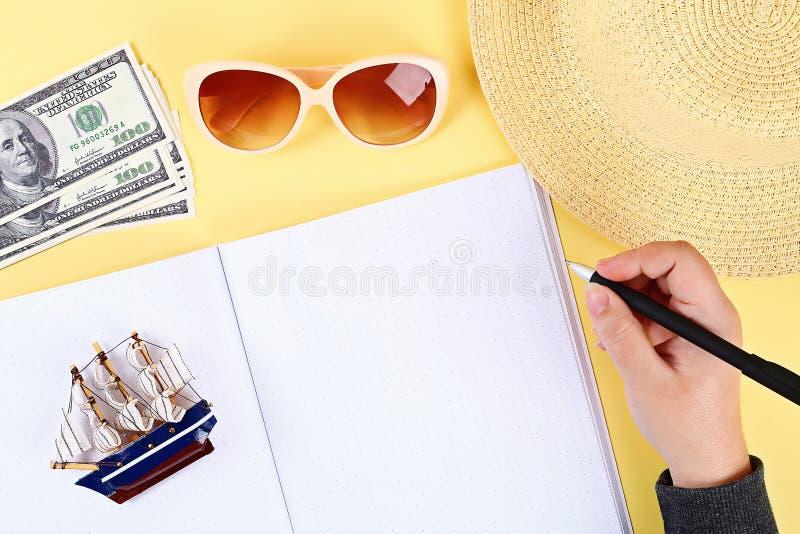 blocnote gele achtergrond, zonglazen, hoed, geld Hoogste mening De ruimte van het exemplaar De zomerachtergrond, reis stock fotografie