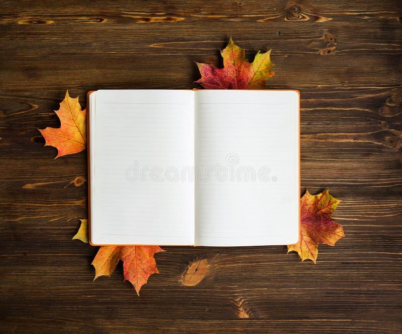 Blocnote met de bladeren van de kleurenesdoorn royalty-vrije stock fotografie