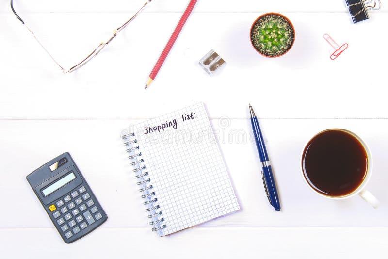 Blocnote met de tekst: een het winkelen lijst Witte lijst met calculator, cactus, notadocument, koffiemok, pen, glazen stock foto's
