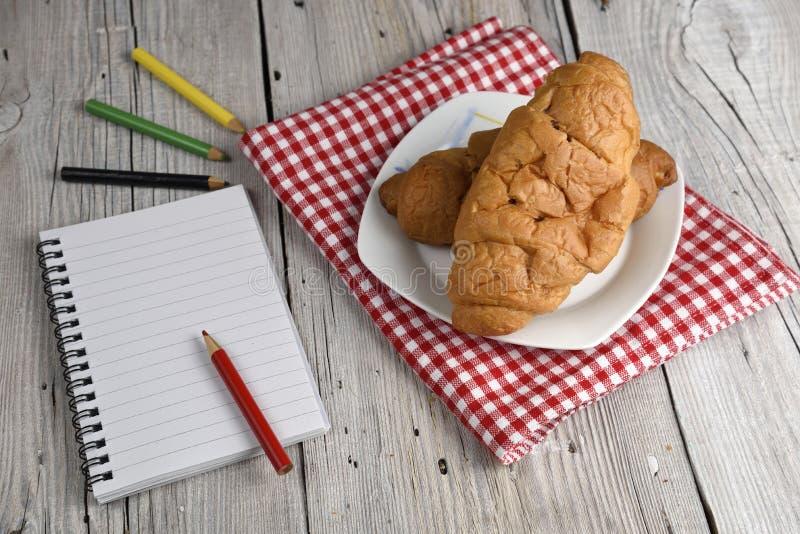 Blocnote met kleurpotloden en croissant stock afbeelding
