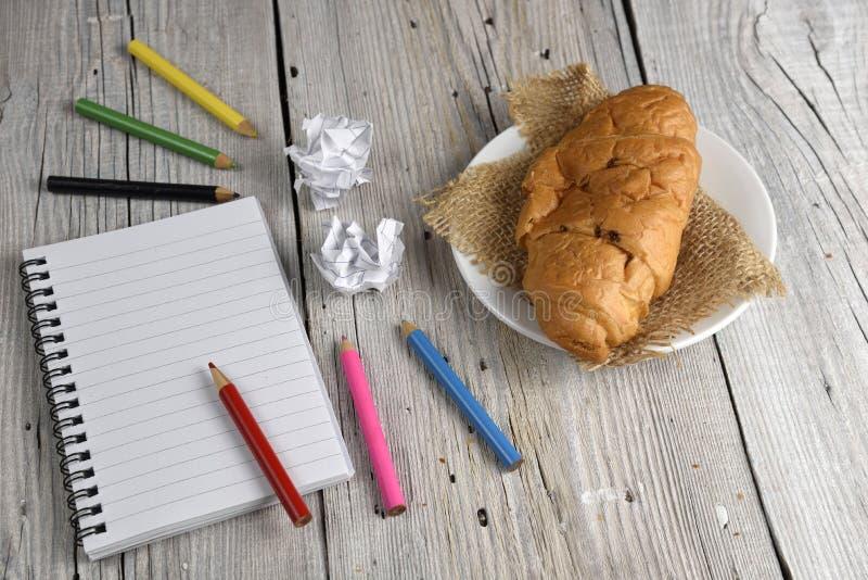 Blocnote met kleurpotloden en croissant royalty-vrije stock afbeelding