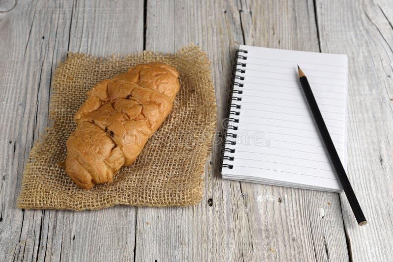 Blocnote met potlood en croissant stock afbeelding