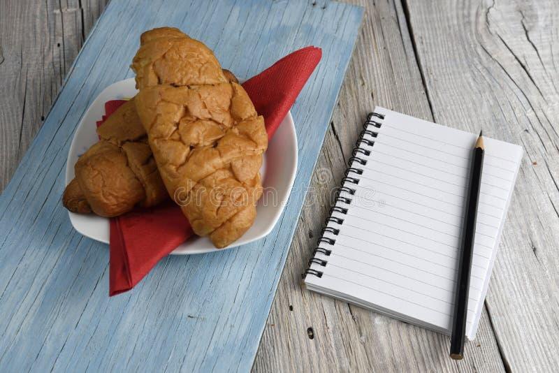 Blocnote met potlood en croissant royalty-vrije stock fotografie