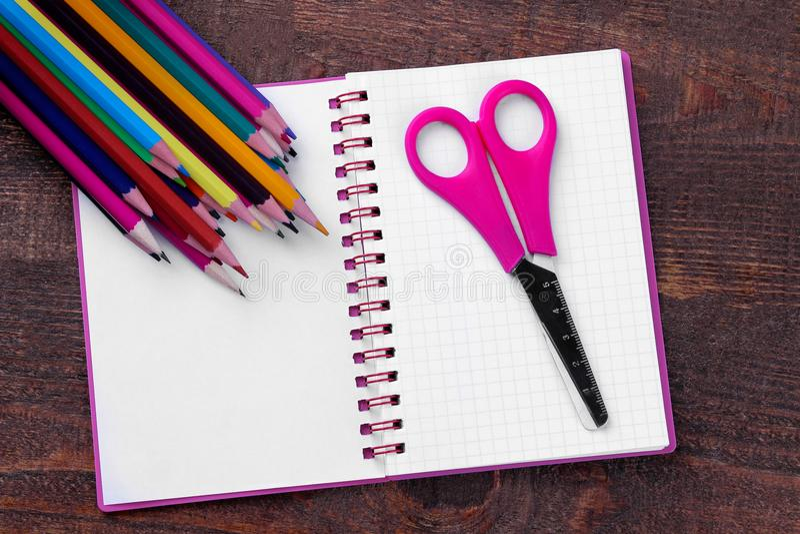 Blocnotepotloden en schaar op een houten bruine lijst Concept onderwijs royalty-vrije stock afbeelding
