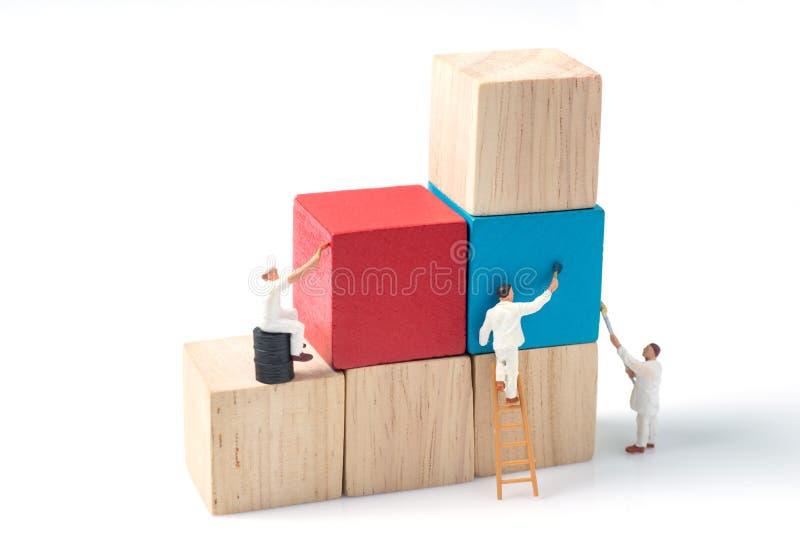 Bloco de apartamentos de madeira do cubo da pintura diminuta do trabalhador dos povos imagens de stock