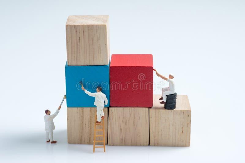 Bloco de apartamentos de madeira do cubo da pintura diminuta do trabalhador dos povos foto de stock