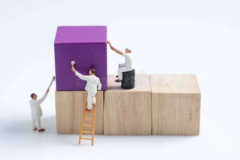 Bloco de apartamentos de madeira do cubo da pintura diminuta do trabalhador dos povos imagem de stock