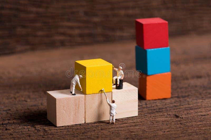 Bloco de apartamentos de madeira do cubo da pintura diminuta do trabalhador dos povos, madeira fotografia de stock royalty free